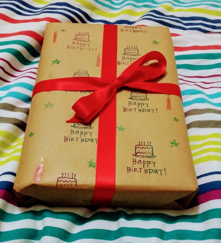 A rectangular gift wrapped in brown paper and stamped with birthday cakes and the message