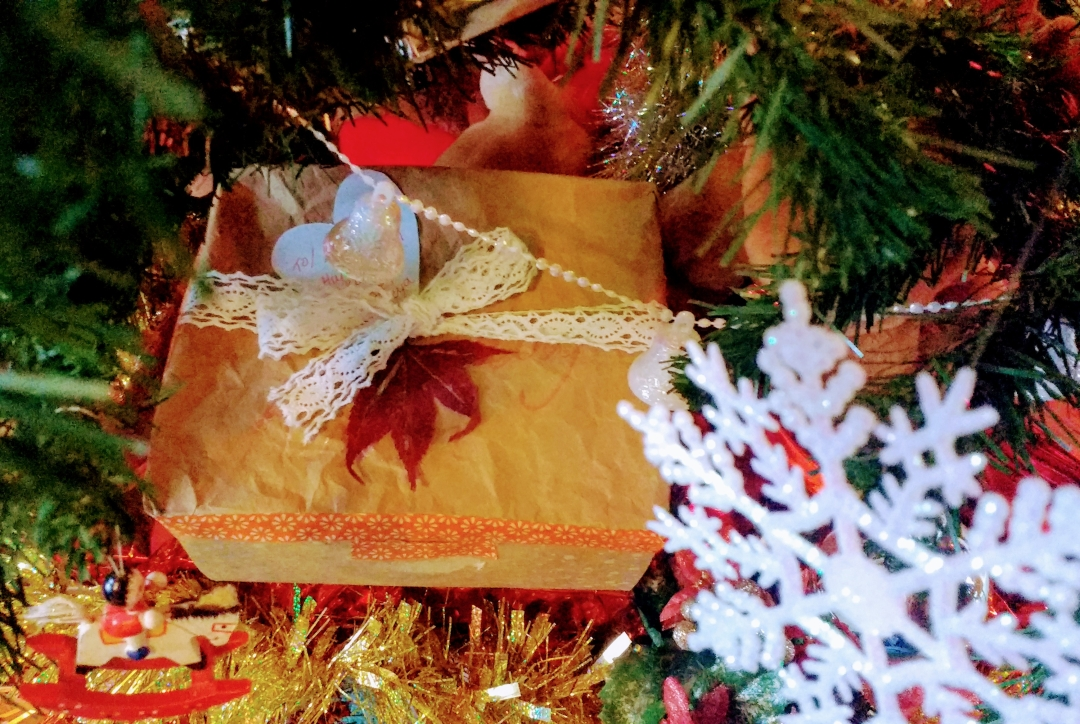 A cardboard gift box is nestled in amongst the boughs of a Christmas tree. A white snowflake dangles in the foreground and other shiny decorations can be glimpsed, including a miniature on a rocking horse. The gift box is decorated with orange washi tape, a cream lacy ribbon and a pressed red leaf.