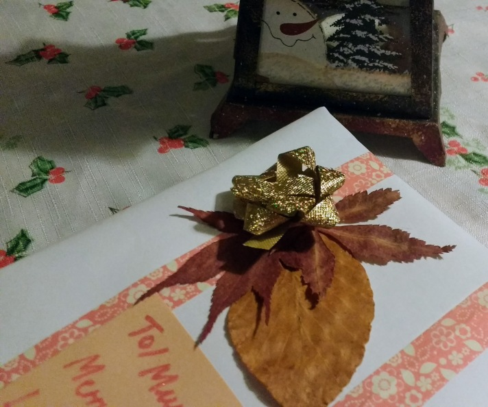 The corner of a gift on a Christmas themed tablecloth with holly on it. The gift has dusky pink washi tape, a gold bow and two pressed autumn leaves. There is a Christmas lantern in the background with a snowman and Christmas tree on it.