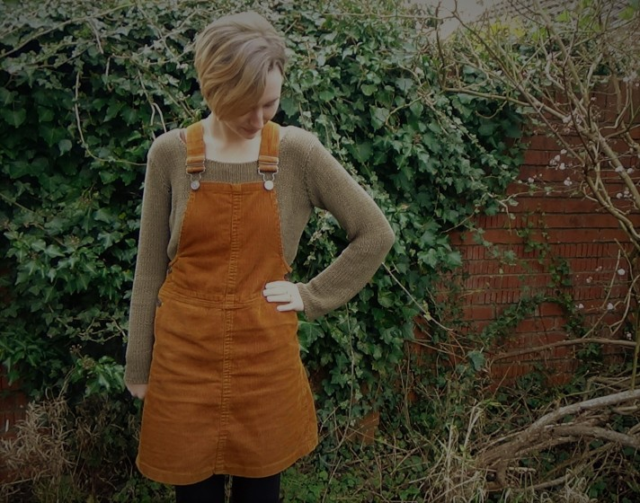 Freya in the garden wearing a khaki green jumper with a rust coloured dungaree dress on top. She is looking down at her outfit.