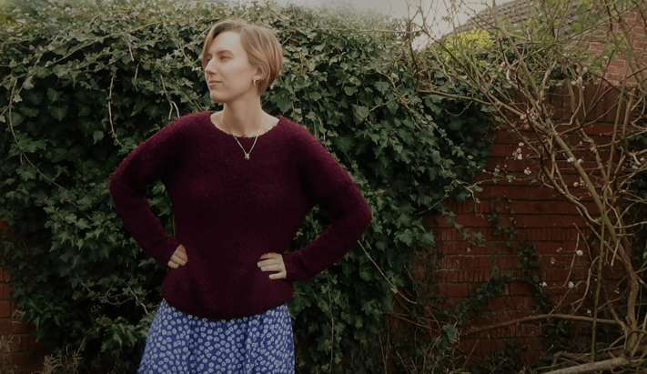Freya stands in the garden wearing a purple fluffy jumper over a blue flowery dress.